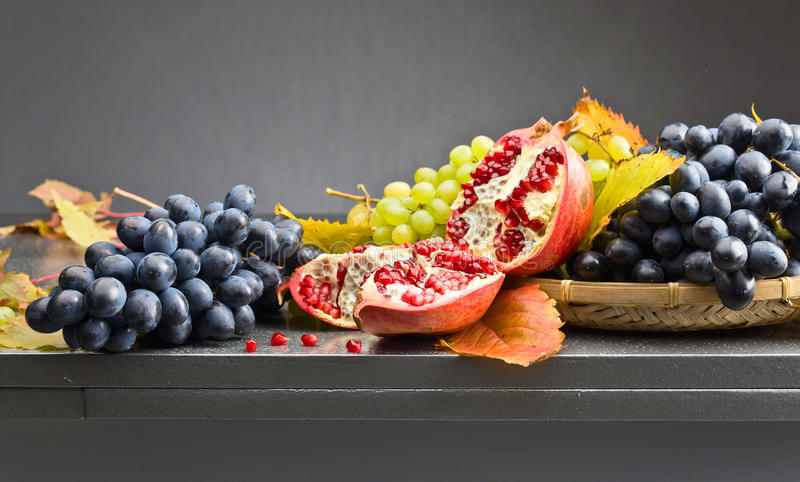Blue and green grapes with pomegranate stock images