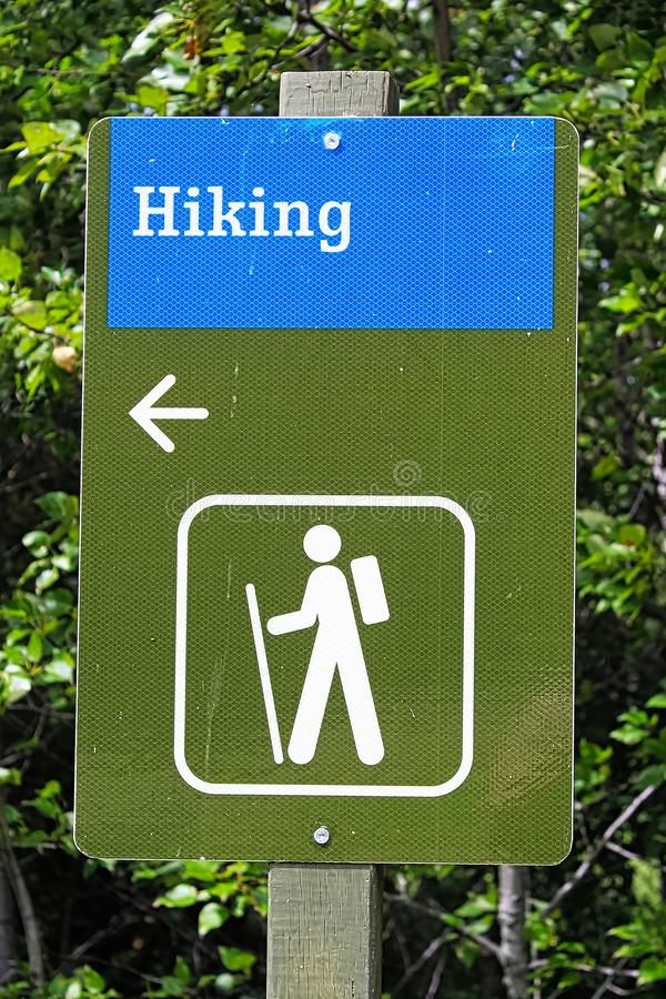A blue and green hiking direction sign with an arrow royalty free stock photos
