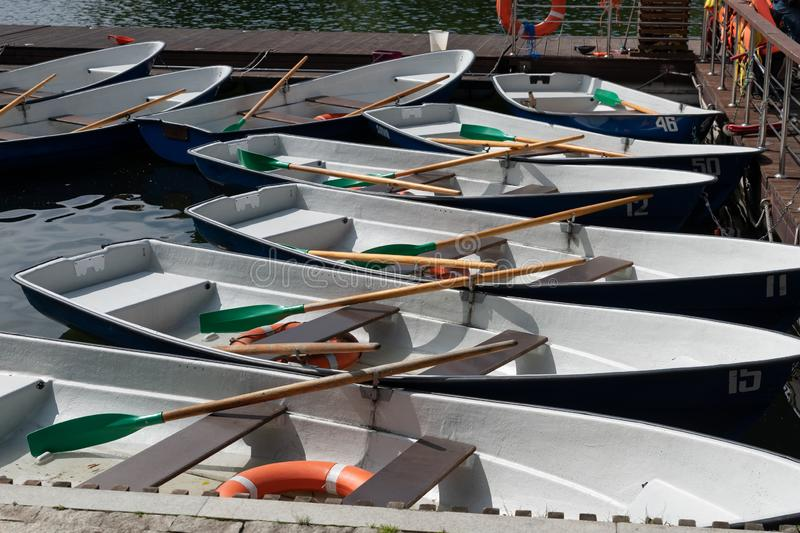 Blue -Green pleasure boats moored at the pier in the Park. Summer skiing on the lake in the Park. Outdoor recreation with family. At the weekend in the fresh royalty free stock photography
