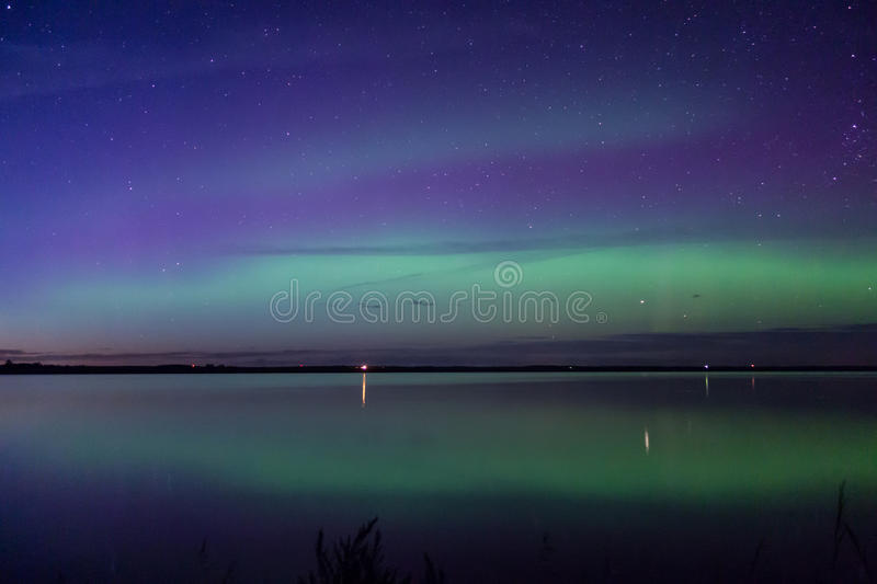 Blue green and purple aurora borealis reflected over a lake stock image