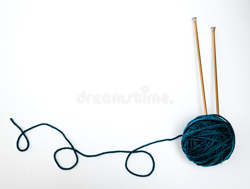 Blue-Green Yarn with Knitting Needles. Ball of yarn with knitting needles stuck in and trailing yarn on white background stock photography