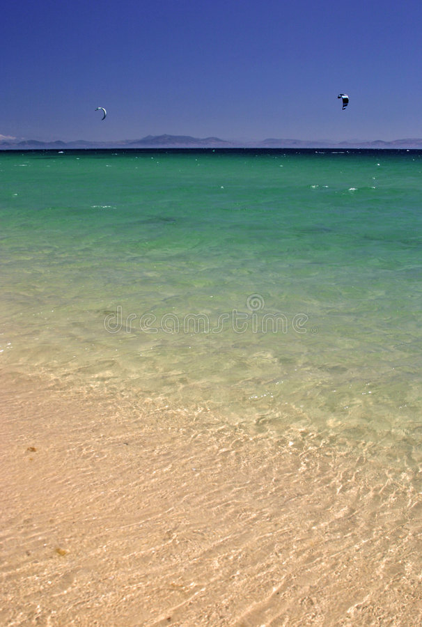 Blue green and yellow colors of a white sandy beach in Spain. stock images