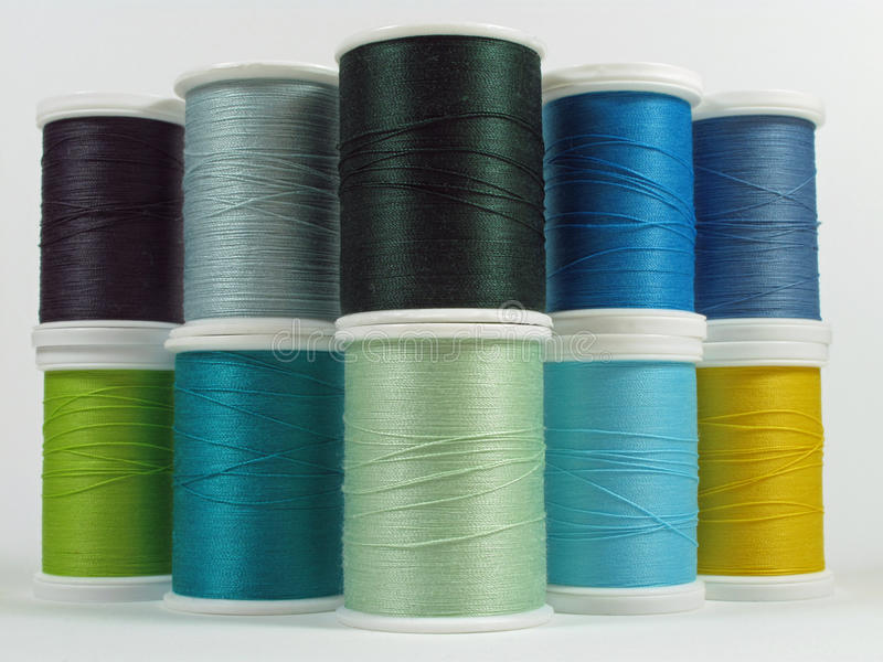 Blue, green and yellow spools of thread stock photos