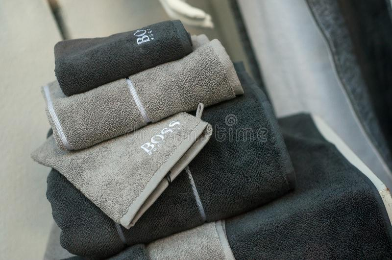 Blue and grey bath towels pile fromn Hugo Boss brand in store showroom stock image