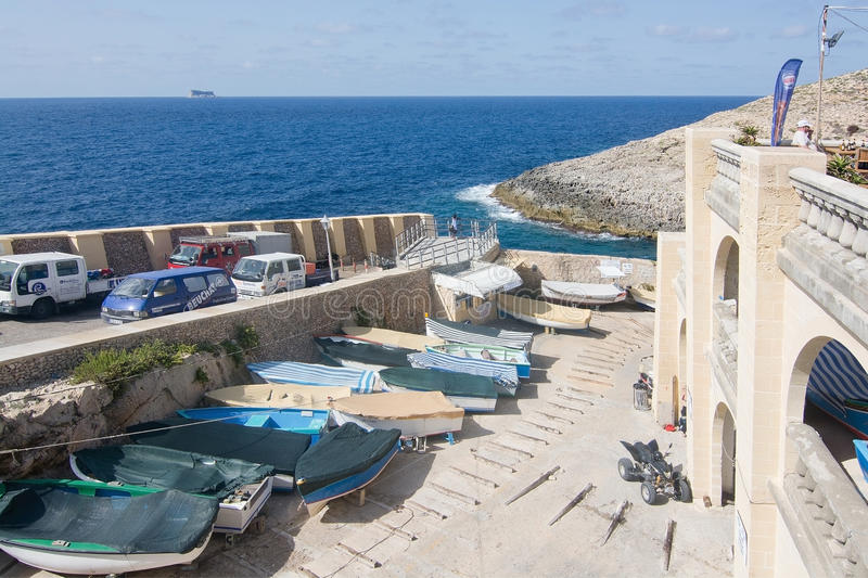 Blue Grotto boats downhill. BLUE GROTTO, MALTA - SEPTEMBER 15, 2015: Boats lying along the downhill street of popular tourist attraction Blue Grotto on a sunny royalty free stock photos