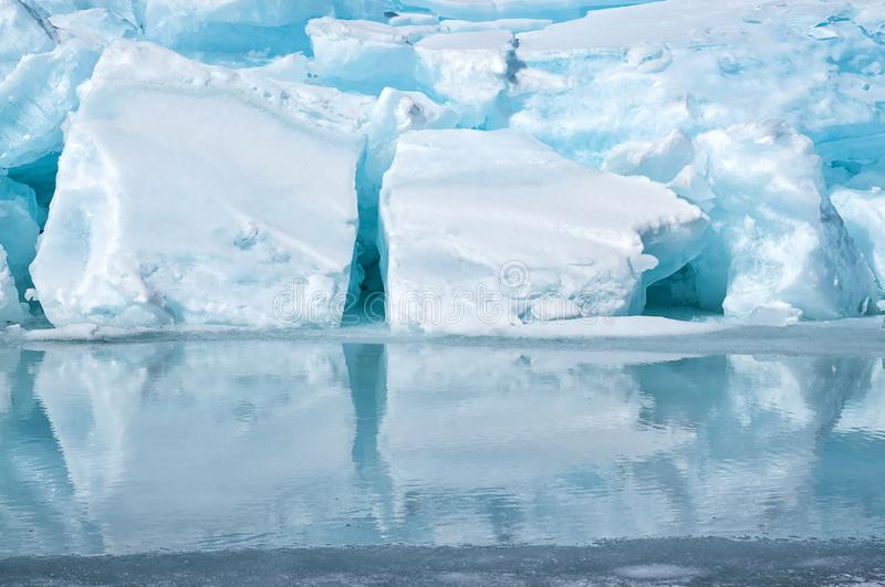 Blue growler piece of iceberg with reflection in calm water. Arctic ocean stock photography