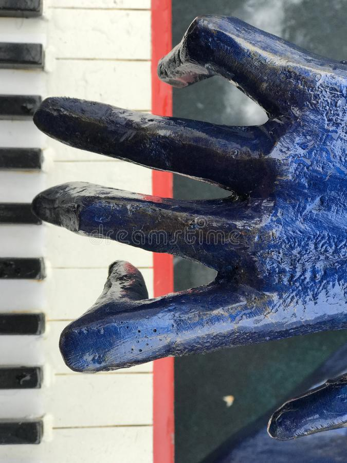 A blue hand plays a piano. A sculpture of a pianist plays a metal instrument with relish royalty free stock images