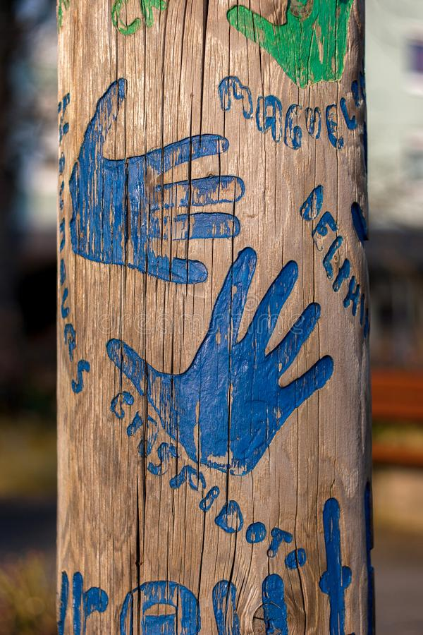 Blue hands on a tree trunk stock image