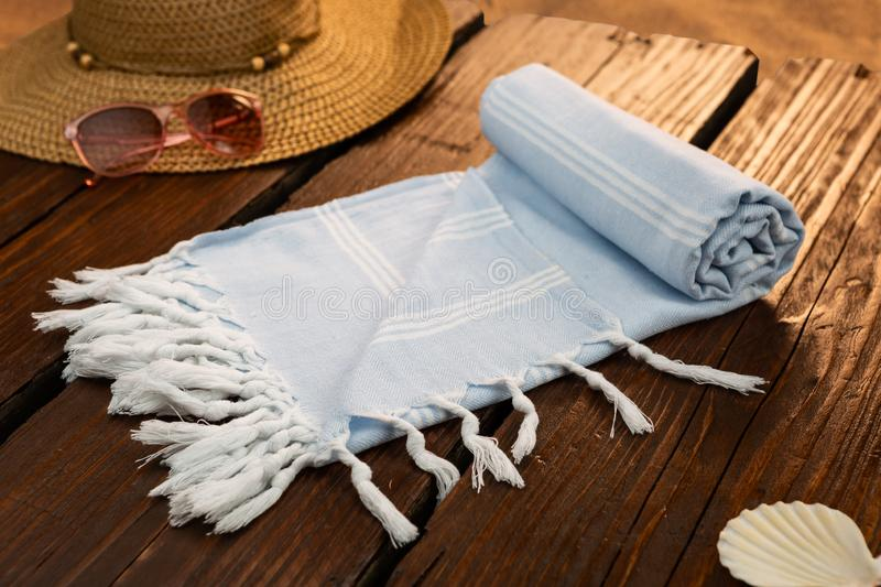 Blue Handwoven hammam Turkish cotton towel on wooden pier. Blue Handwoven hammam Turkish cotton towel on the beach with sun hat, sunglasses and shell beside stock images