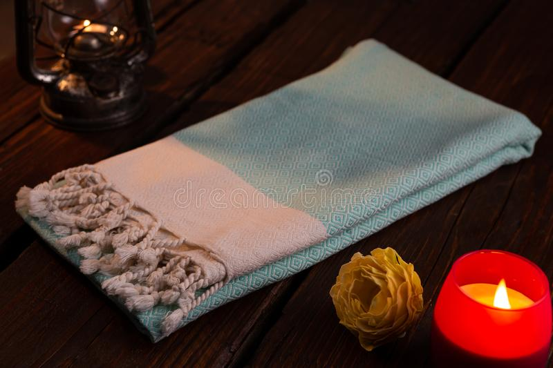 Blue Handwoven hammam Turkish cotton towel on dark wooden background. With, candle, yellow rose and lantern beside stock photography