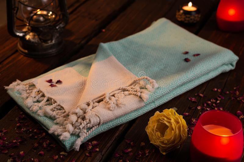 Blue Handwoven hammam Turkish cotton towel on dark wooden background surrounded by dried rose petals. Blue Handwoven hammam Turkish cotton towel on dark wooden stock images