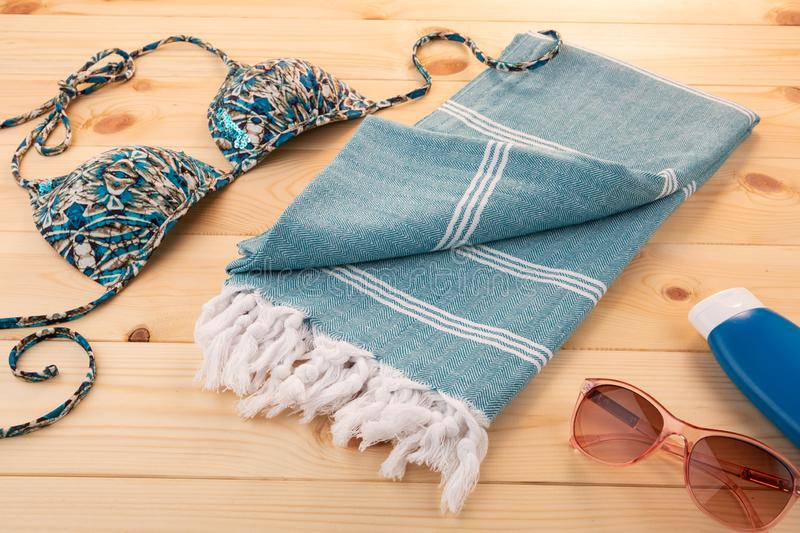 Blue Handwoven hammam Turkish cotton towel. Handwoven hammam Turkish cotton towel on light wooden background with bikini and sunglasses on the side stock images