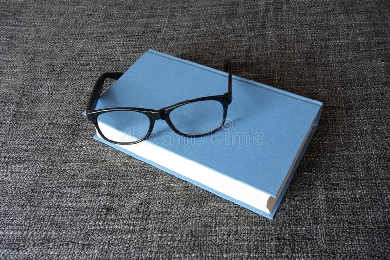 Book and reading glasses on a grey background stock images