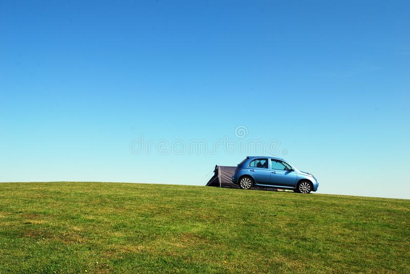 Blue Hatchback On Green Grass Field Under Blue Sky royalty free stock photos