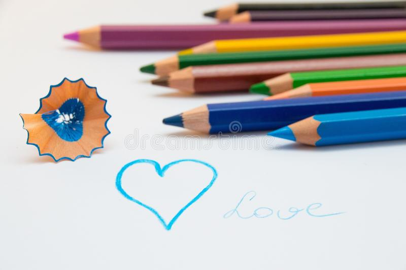 Blue heart and colored pencils stock photos