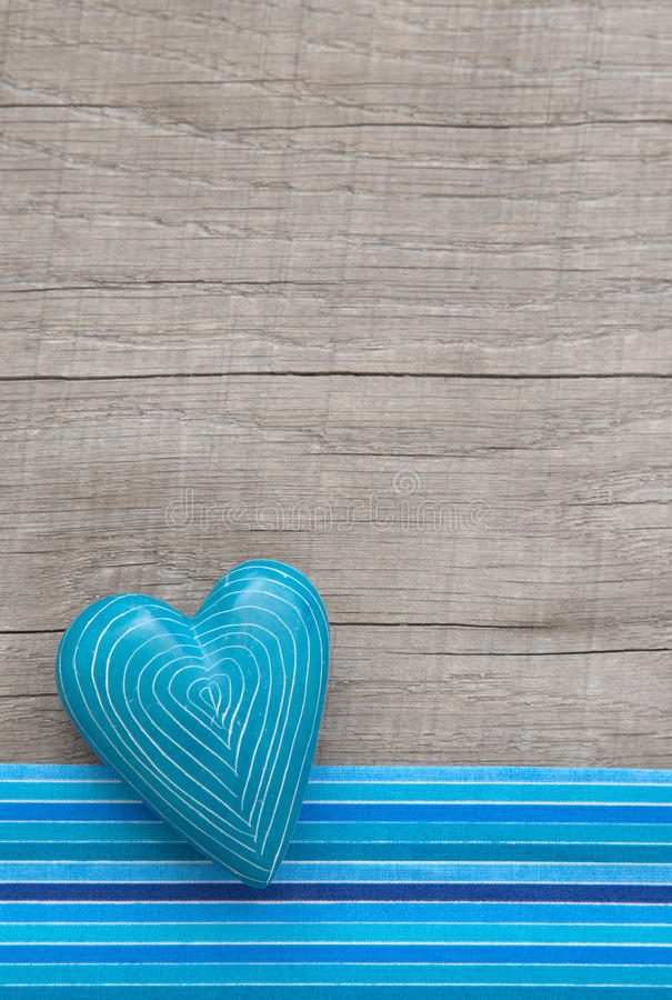 Blue heart with symmetric carved lines on grey wooden background royalty free stock photo