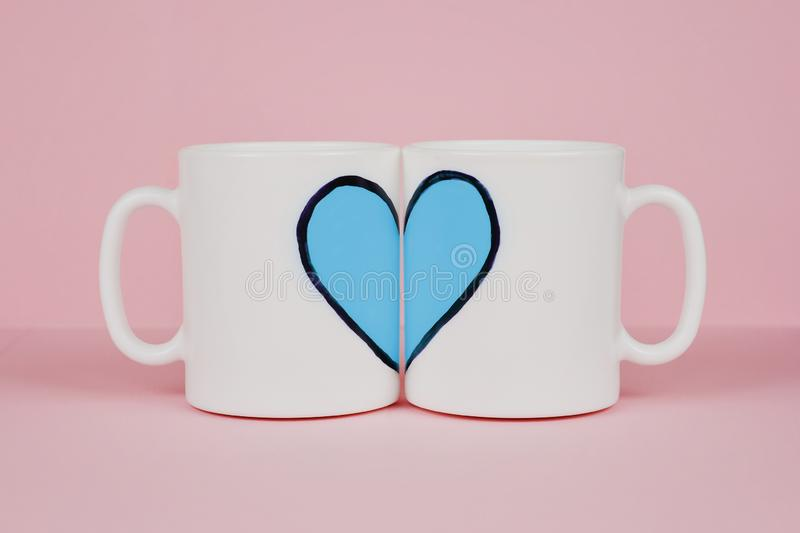 Blue heart and two cups on pink background. Valentine`s day, love, wedding concept royalty free stock photography