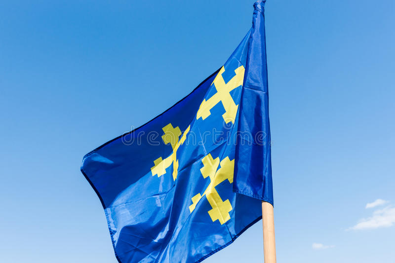 Blue heraldic flag. Knightly heraldic flag of blue and yellow colors with three yellow crosses waves in the breeze against the background of blue sky stock photo