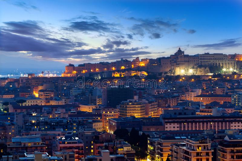 Cagliari turns on the lights, Sardinia. Blue hour in Cagliari, scenic sky, city illumination royalty free stock images