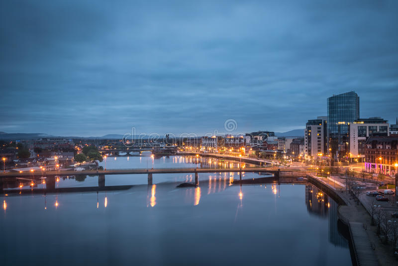 Blue hour in Limerick city. View of the bridges over river Shannon, hotels and commercial buildings in Limerick town after sunset, Ireland royalty free stock photography