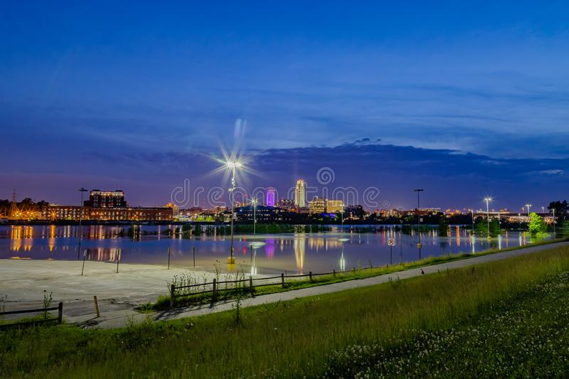 Blue hour night time photo of Omaha Nebraska Riverfront. Blue hour night time photo of down town Omaha Nebraska with reflections in the swollen Missouri River at royalty free stock photography