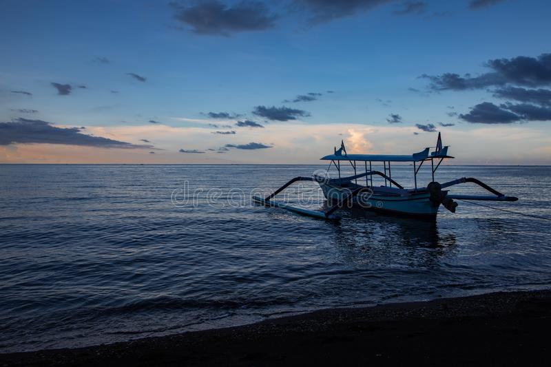 Blue hour over calm ocean and black sand beach with balinese boat royalty free stock image
