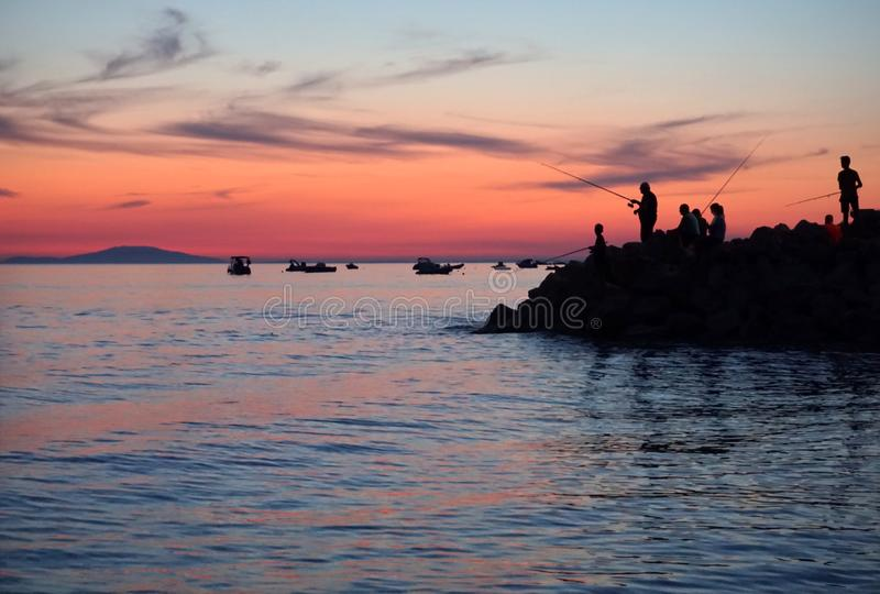 Silhouette of young and old people fishing on the peninsula in the beautiful summer sunset in blue and purple color tone stock images