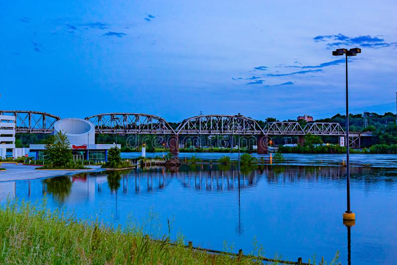 Blue hour scene of flooded Harrah`s Casino parking lot with reflections of Union Pacific railroad bridge. In Council Bluffs Iowa. Swollen Missouri river and royalty free stock photo