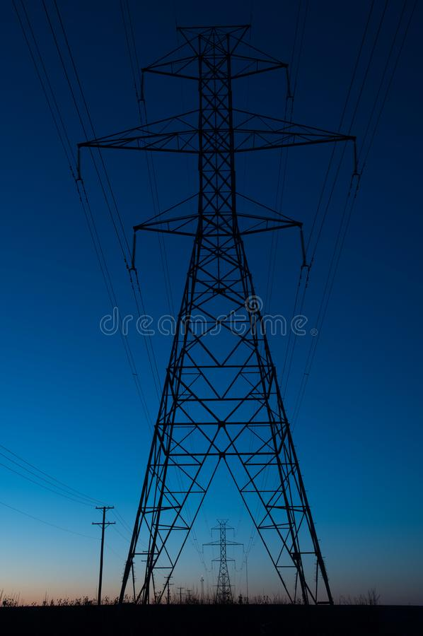 Blue hour silhouette of a power line tower royalty free stock photo