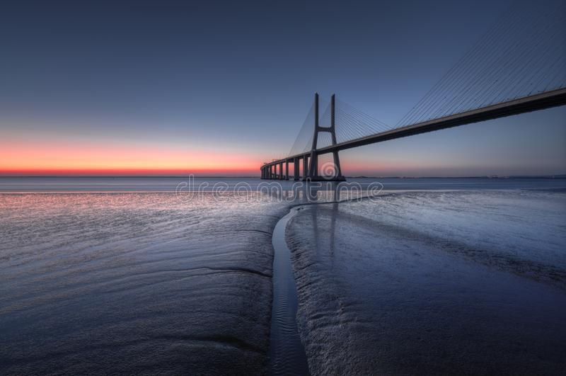 Blue hour at Vasco de Gama Bridge in Lisbon. Ponte Vasco de Gama, Lisboa, Portugal. Peaceful atmosphere at Vasco de Gama Bridge in Lisbon during sunrise. Ponte royalty free stock images