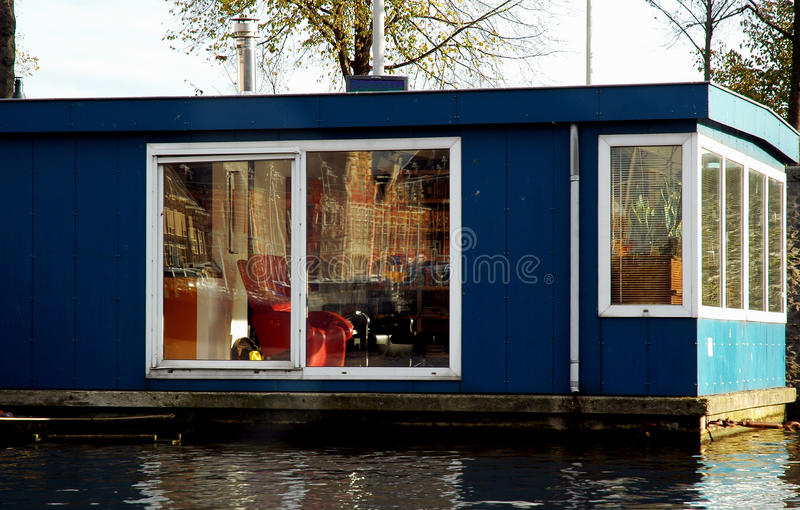 Blue House Boat with Red Armchair. In a dutch canal. Amsterdam Central Station refection on big glass window stock photos