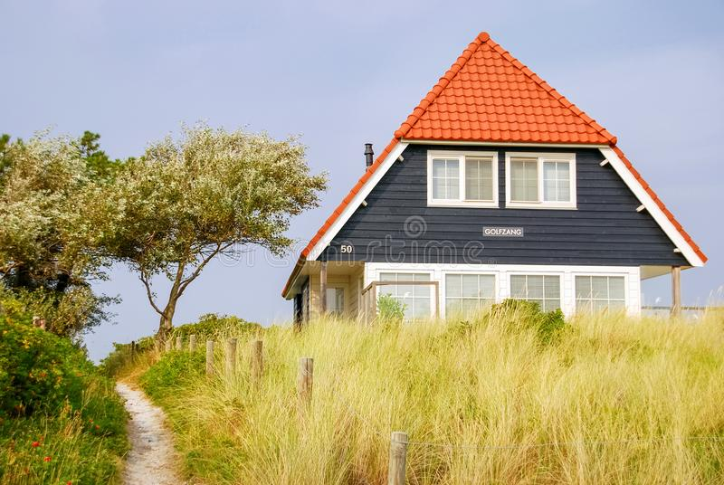 Blue house on the Island of Vlieland. A blue house and the Dutch flag on the Frisian Island of Vlieland, The Netherlands. The Frisian Islands, are also known as stock photos