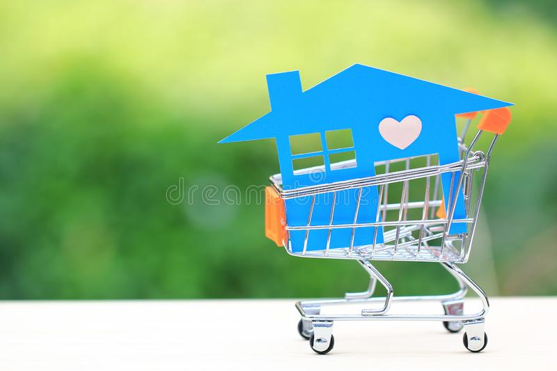 Blue house model on mini shopping cart on natural green background, Business investment and Real estate concept.  stock image
