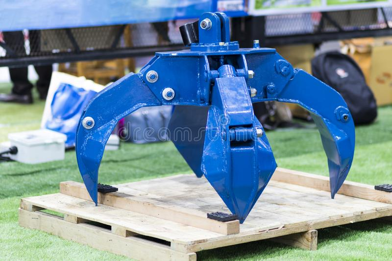 The blue hydraulic manipulator  for loading steel scrap metal. Close up crane loader machine bucket background industry isolated tree work construction stock image