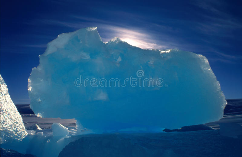 Blue Ice Block. A large block of ice back-lit by the sun. The block of ice fell off an iceberg which was trapped in sea ice along the coast of Antarctica stock photography
