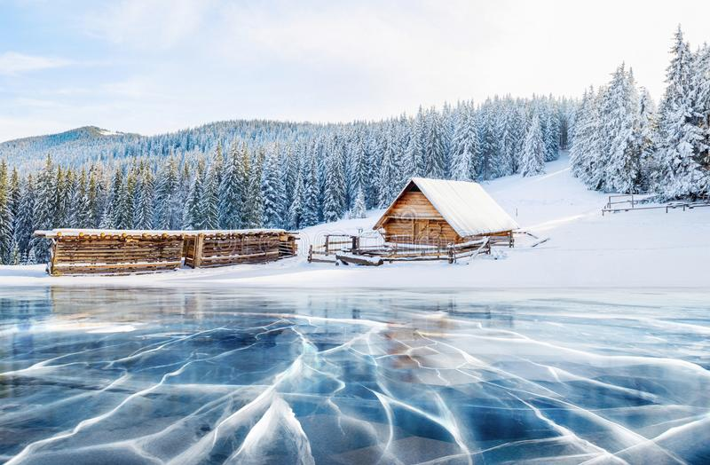 Blue ice and cracks on the surface of the ice. Frozen lake under a blue sky in the winter. Cabin in the mountains royalty free stock photos