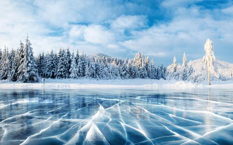 Blue ice and cracks on the surface of the ice. Frozen lake under a blue sky in the winter. The hills of pines. Winter. Carpathian, Ukraine, Europe stock photography