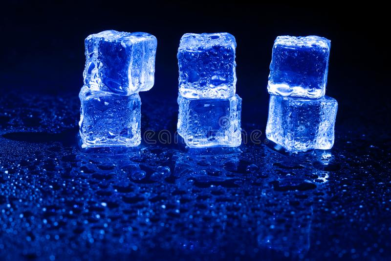 Blue ice cubes on black background. Blue  ice cubes on black background, alcohol, alcoholic, amber, bar, beverage, bottle, bourbon, brandy, brown, close-up royalty free stock photo