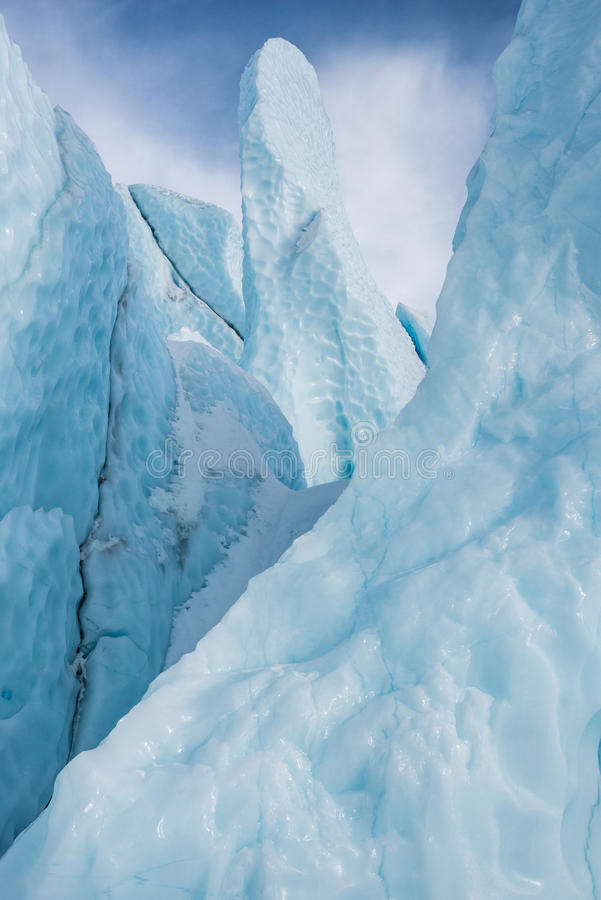 Blue Ice 10,000 year old glacier alaska. Blue ice 10,000 year old form pinnacles and sharp shards and towers rising from the front of the glacial flow. alaska stock photo