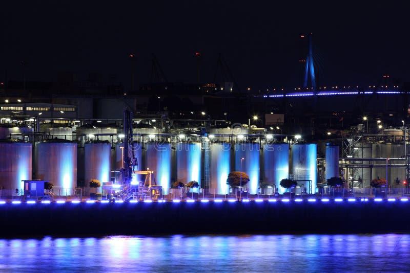 Blue illuminated industry at night. Blue industrial plant at night in port of Hamburg stock photo