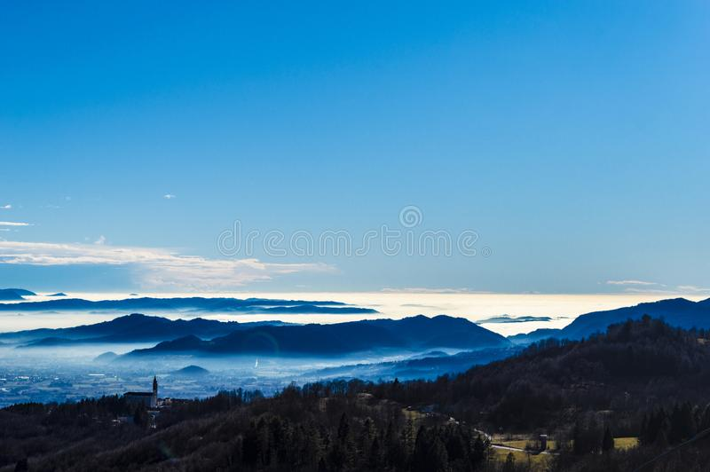 Blue infinite fairytale. Breathtaking view to Tretto di Schio, Italy, in the background the Po valley with the typical spring fog and an  campground id a royalty free stock photos