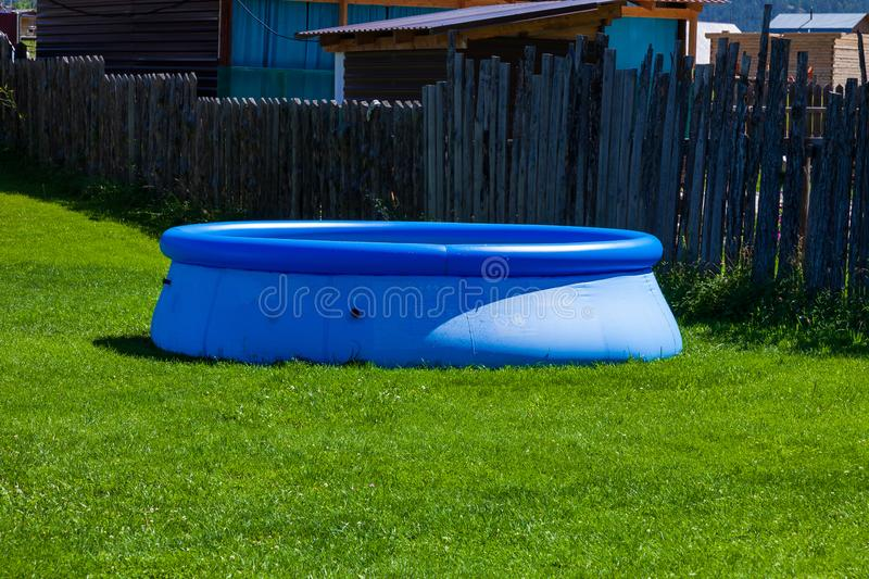Blue inflatable rubber pool on a lawn of green grass in the courtyard of a country house with a wooden fence on a background of. Mountains and blue sky stock image