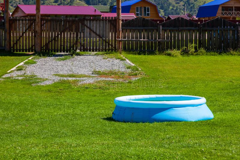 Blue inflatable rubber pool on a lawn of green grass in the courtyard of a country house with a wooden fence on a background of. Mountains and blue sky stock photo