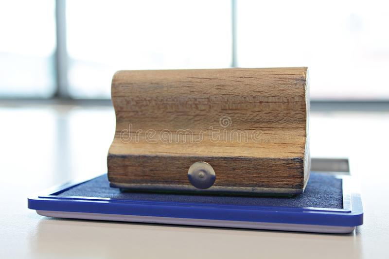 Blue ink color stamp box and wooden rubber stamp on the table. Wooden rubber stamp with blue ink color stamp pad on the table royalty free stock photo