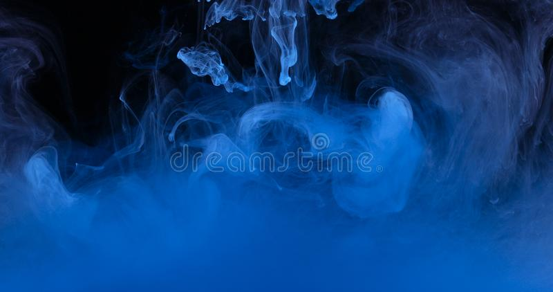 Blue Ink Colors in Water Creating Liquid Art Shapes stock image