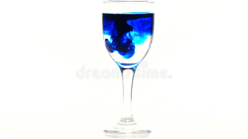 Blue ink dropping into a glass of water on a white background stock images