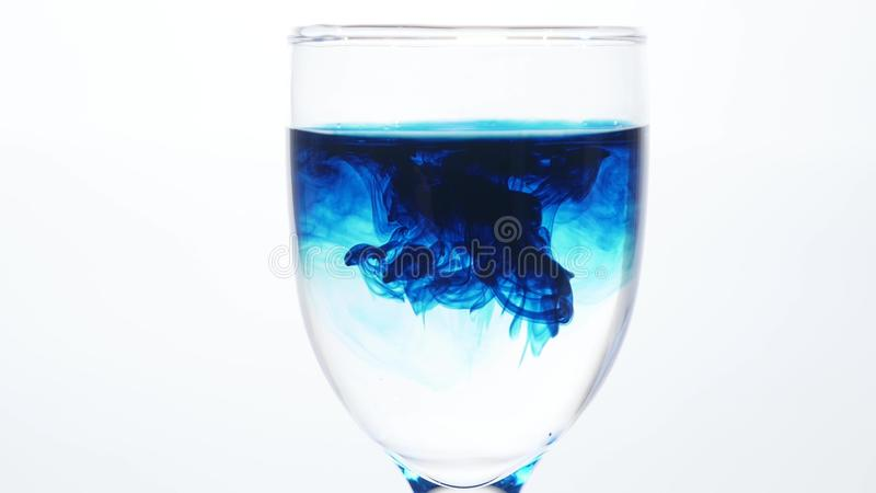 Blue ink dropping into a glass of water on a white background. The poison in the glass concept. royalty free stock image