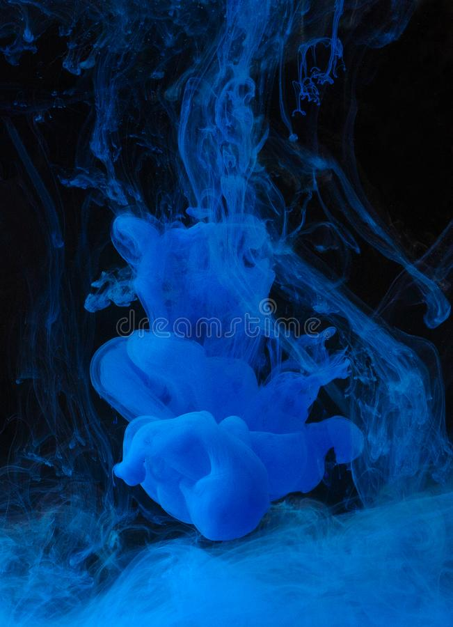 Blue ink in water on black background. Blue ink in water on black background, creative abstract backdrop stock image
