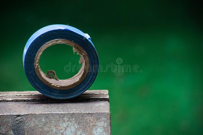 Blue insulating tape on a metal vice. And green background, sticky, plastic, adhesive, insulation, roll, protection, tool, fix, circle, object, industry, rubber royalty free stock image