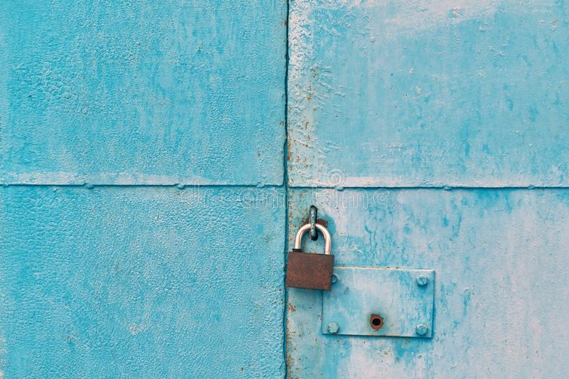 The blue iron gate is closed with a padlock stock images